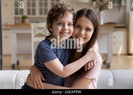 Assis sur la table à la jeune mère embrassant son fils d'âge préscolaire