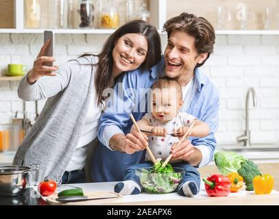 Mère de prendre avec bébé selfies fils et mari à la cuisine Banque D'Images
