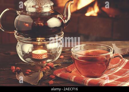 Plateau avec l'aubépine dans un verre tasse et théière avec un photophore sur une table en bois dans une chambre avec une cheminée. Banque D'Images