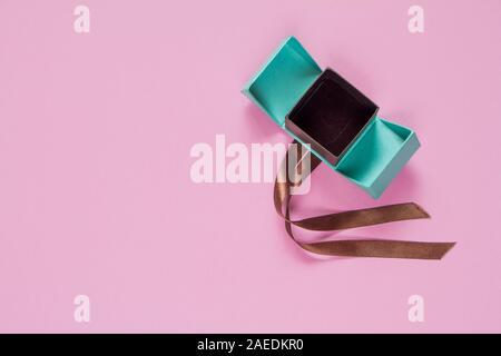 Turquoise ouvert cadeau ou présent fort avec ruban brun sur rose Vue de dessus de table. Mise à plat. Anniversaire, un mariage ou Noël concept. Banque D'Images
