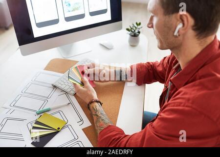 High angle portrait of tattooed man holding tout en choisissant des échantillons de couleurs de la palette de couleurs web design project, copy space Banque D'Images