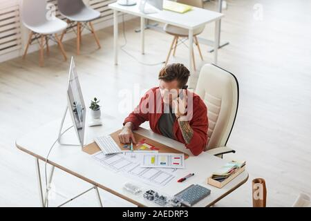High angle portrait of businessman speaking tatoué contemporaine par téléphone tout en travaillant au bureau en bureau spacieux, copy space Banque D'Images