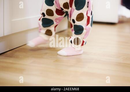 Bébé de 1 an marche sur plancher en bois stratifié dans une chambre à coucher. toddler walking wobbly dans l'exercice pratique. développement des enfants et à la famille des co
