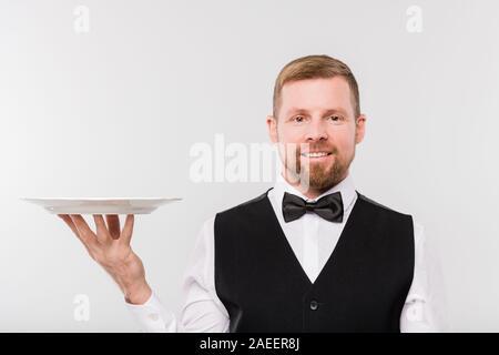 Heureux jeune serveur en nœud papillon et gilet noir holding white assiette propre