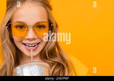 Jolie petite fille avec ses lunettes boit un cocktail et sourires isolé sur fond blanc Banque D'Images