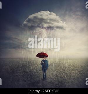 Scène surréaliste où l'homme se tient à l'extérieur sous l'égide d'une seule tempête de pluie nuages mystérieux que sur lui. Trouver une solution à la crise d'échappement situatio