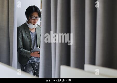 Jeune homme asiatique à lunettes et avec des écouteurs occupé à lire un livre
