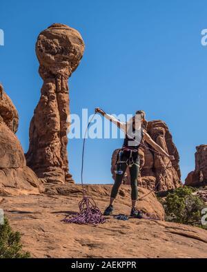 Une jolie jeune femme se prépare à une escalade dans le jardin d'Éden dans Arches National Park près de Moab, Utah. Banque D'Images