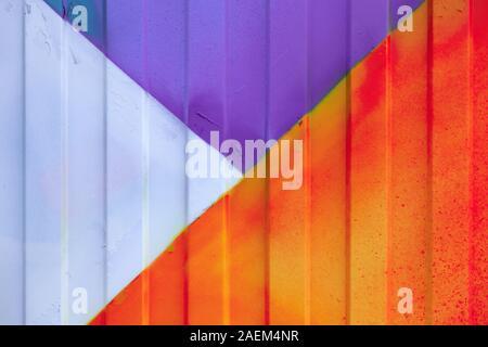 A l'arrière-plan d'un profil en métal peint en violet, orange, rouge et blanc sur la clôture ou le contenant. La construction dans la ville. Banque D'Images