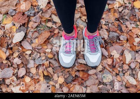 Close-up de pieds d'un coureur s'exécutant dans les feuilles d'automne dans le parc