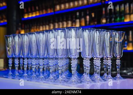 Beaucoup de verres de champagne se tient debout sur une table en verre, transparente. Banque D'Images