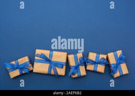 Du papier Craft cadeaux enveloppés dans une rangée sur fond bleu, mise à plat avec l'exemplaire de l'espace. Résumé de Noël des maquettes. Banque D'Images