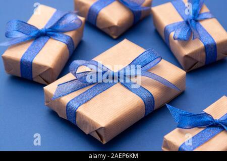 Close up des boîtes-cadeaux, cadeaux. Cadeaux artisanat enveloppé dans du papier sur fond bleu. Banque D'Images
