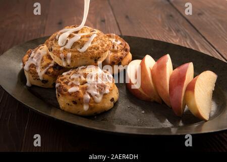 Un concept food photo de cinaamon avec rouleaux vitrage étant répandues et sur des tranches de pomme. Banque D'Images
