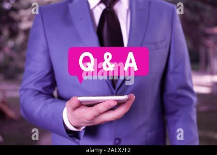Signe texte montrant Q et R. photo d'affaires texte défini en questions posées et réponses Businessman in blue suite se distingue avec un téléphone mobile dans la main Banque D'Images