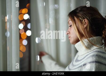 Triste femme seule se plaindre standing looking at les lumières de la ville, à travers une fenêtre dans la nuit à la maison Banque D'Images