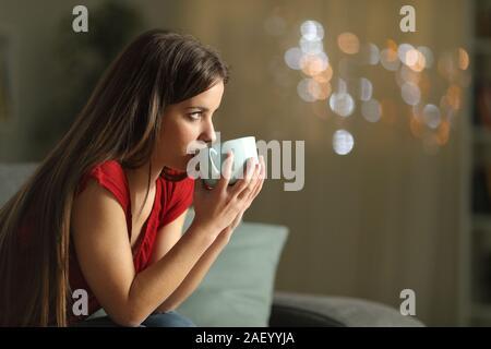 Vue latérale du portrait d'une femme à la recherche de là à boire du café assis sur un canapé dans la nuit à la maison
