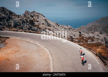 L'homme et la femme ride ensemble à vélo dans les montagnes, couple actif sur la route. Banque D'Images