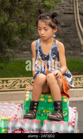 Jeune fille assise sur le chariot des boissons à l'extérieur de la Cité Interdite, Pékin, Chine Banque D'Images