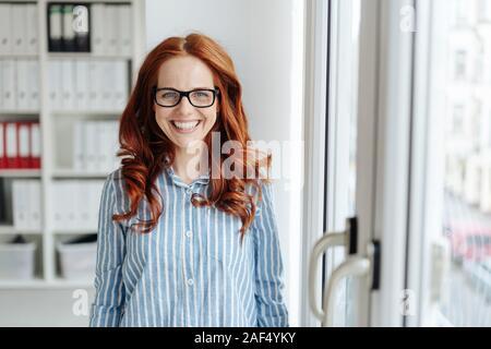 Friendly young businesswoman avec un large sourire chaleureux à l'intérieur du verre à côté d'une porte d'entrée à l'office Banque D'Images