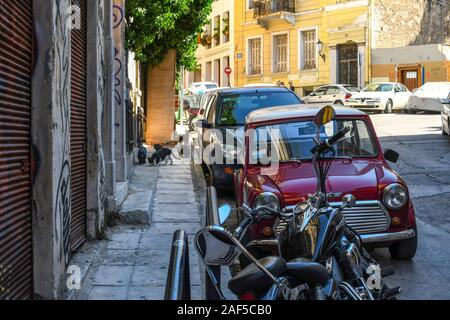 Un groupe de chats sort d'une attente dans un mur sur un trottoir dans la région de Plaka d'Athènes, Grèce.