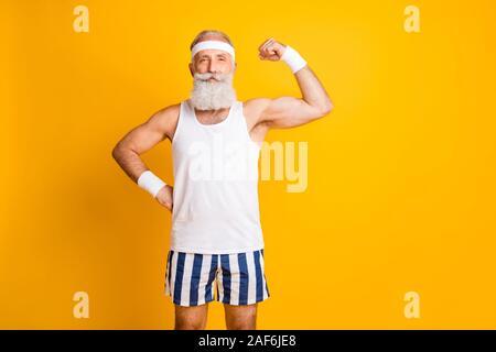 Photo de cheerful attractive positive beau vieil homme démontrant ses muscles à attentivement à vous tenir la main sur la taille de couleur vive isolé Banque D'Images
