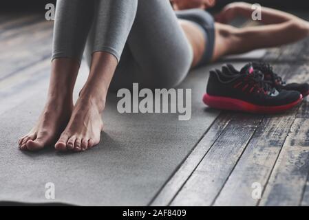 Droit axé sur les jambes. Fille avec corps mince travaille sur l'abs lorsque couché sur le plancher Banque D'Images