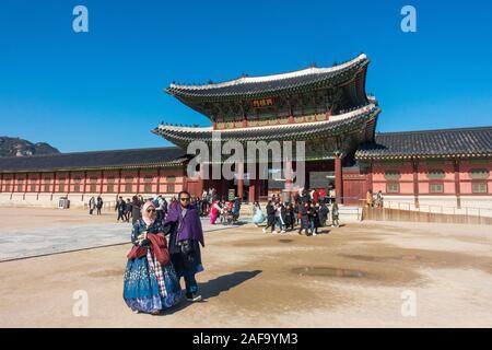 Séoul, Corée du Sud - Novembre 28th, 2019: les touristes portant robe Hanbok traditionnel coréen et à visiter le Palais Gyeongbokgung sur un jour d'hiver ensoleillé Banque D'Images