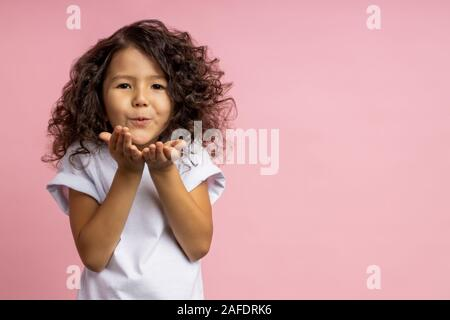 Jolie petite fille de race blanche avec curly hairstyle dans blanc t shirt, soufflant de l'air kiss plus de palmiers, exprimer l'amour, isolé sur fond de studio rose Banque D'Images
