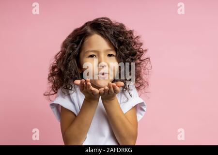 Photo de gros plan belle race blanche timide petite fille avec la peau brune soufflant de l'air kiss from open palms à l'appareil photo, l'expression de l'amour d'amis, plus isolées Banque D'Images