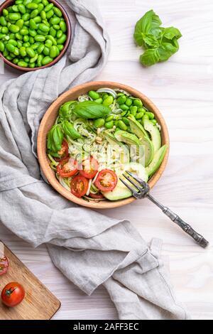 Une salade fraîche, saine avec zoodles nouilles aux courgettes, tomates, avocat et bébé edamame beans. La salade n'est dans un bol en bois sur un tableau blanc. Il y Banque D'Images