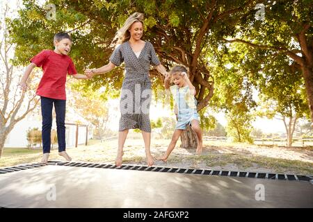 Mère jouant avec des enfants sur d'extérieur dans le jardin