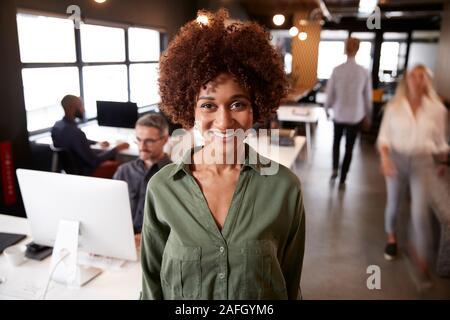 Femelle noire millénaire creative debout dans un bureau temporaire occupé, souriant à l'appareil photo Banque D'Images
