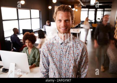 Mâle blanc millénaire creative debout dans un bureau temporaire occupé, souriant à l'appareil photo
