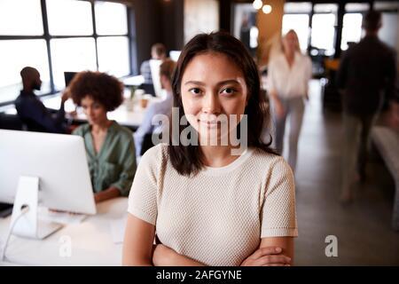 Femme Asiatique millénaire creative debout dans un bureau temporaire occupé, souriant à l'appareil photo