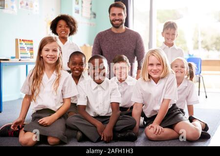 Portrait des élèves de l'élémentaire en uniforme assis sur le plancher en classe avec des mâles. Banque D'Images