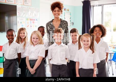 Portrait des élèves de l'élémentaire en uniforme debout en classe avec des enseignants de sexe féminin Banque D'Images
