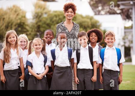 Portrait de plein air les élèves de l'élémentaire avec l'enseignant en uniforme debout sur terrain de jeu Banque D'Images