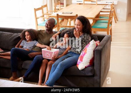 Family Sitting on Sofa At Home Eating Popcorn et regarder ensemble
