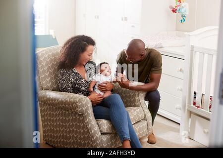 Les parents aimants Sitting in Chair de câliner Bébé en maternelle à la maison Banque D'Images