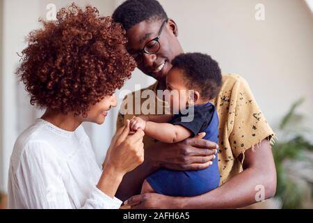 Les parents aimant jouer avec bébé nouveau-né à la maison dans cet appartement Loft Banque D'Images
