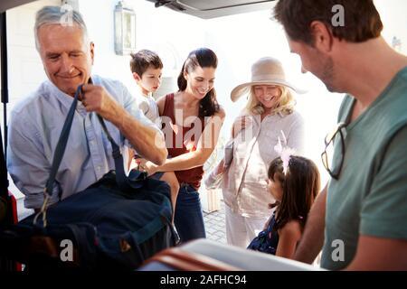 Grand-père et père de démarrage voiture d'emballage de vacances avec assurance, tandis que la famille d'attendre à proximité, Close up Banque D'Images