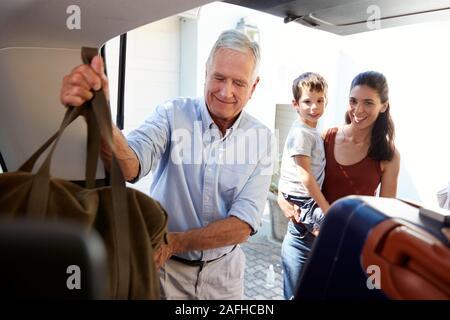 Hauts homme blanc voiture d'emballage de démarrer avec une assurance, regardée par son petit-fils et sa fille adulte Banque D'Images