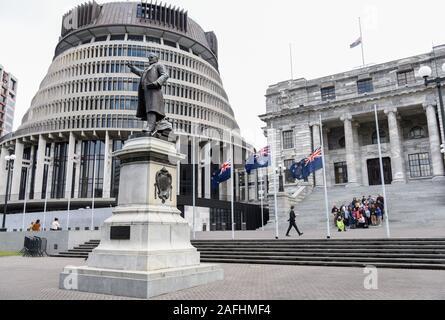 Wellington, Nouvelle-Zélande. Dec 16, 2019. La Nouvelle-Zélande drapeaux en berne devant les édifices du Parlement pour commémorer les victimes de l'éruption volcanique de l'Île Blanche à Wellington, Nouvelle-Zélande, le 16 décembre 2019. Des questions doivent être posées et répondues en ce qui concerne les pertes humaines causées par l'éruption volcanique de l'île Blanche, a déclaré le Premier Ministre néo-zélandais Jacinda Ardern lundi. Les gens à travers la Nouvelle-Zélande a fait observer une minute de silence lundi en hommage aux victimes de l'éruption volcanique de l'Île Blanche. Credit: Guo Lei/Xinhua/Alamy Live News