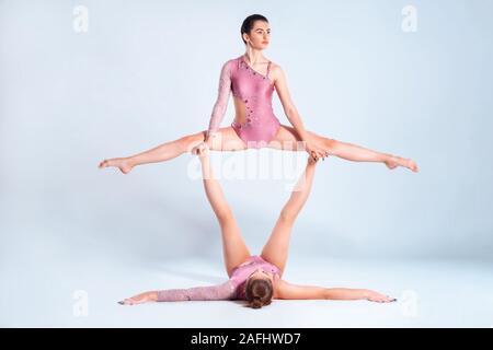 Deux gymnastes filles flexibles avec des nattes, en rose justaucorps sont l'exécution par le biais d'appuyer tout en se posant isolé sur fond blanc. Close-up. Banque D'Images
