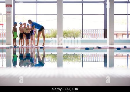 Entraîneur féminin donne aux enfants en cours de natation Briefing, assis sur le bord d'une piscine intérieure