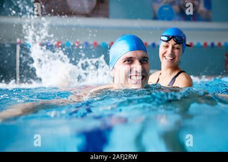 Une femme professeur donnerait un homme d'une leçon en piscine