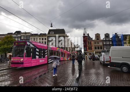 Amsterdam, Pays-Bas, août 2019. Jour de pluie dans la vieille ville. Les silhouettes des gens et des choses se reflètent sur la route mouillée. Les gens traversent la croix Banque D'Images