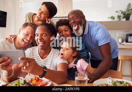 Portrait Mixed Race Family Posing for qu'ils mangent Selfies Table repas autour d'ensemble, à la maison Banque D'Images