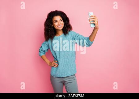 Photo de curly wavy cheerful nice jolie femme debout en toute confiance avec les mains sur la taille prise téléphone pour envoyer des selfies isolés dans un pantalon gris